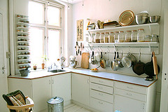 Photo of a white kitchen lit with windows. Rows of glass jars line shelves over the countertop, and a hanging rack of pans and pots appears beneath that.