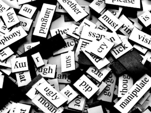 Photo of a jumble of magnetic words used for fridge poetry sets