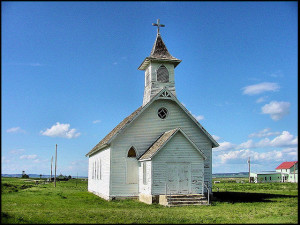 Photo of old white clapboard church building against blue sky
