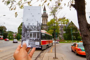 Photograph of a hand holding a vintage photo of a streetcar, lined up with the contemporary shot of the same location with streetcar in present day
