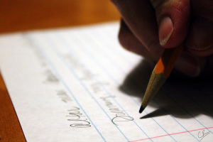 Photo of a hand holding a pencil, writing on a piece of notebook paper