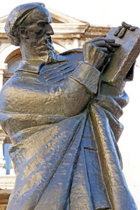 Photo of a bronze statue of a standing man in robes  writing on a tablet
