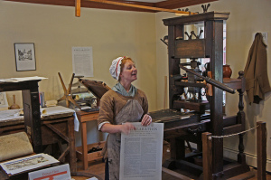 Photo of a woman in period costume and bonnet standing in front of an antique printing press, holding a portfolio-sized page of the Declaration of Independence