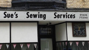 """Photo of a store front.  The name of the store is """"Sue's Sewing Services"""""""