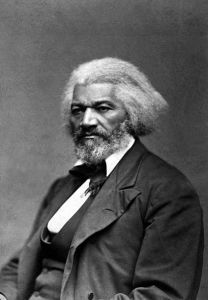 Black and white photograph of Frederick Douglass.  He is seated, wearing a suit, appears as an older man, and is looking off to the left of the camera