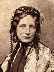 Sepia-toned photo of Harriet Beecher Stowe as a head shot.  She is wearing a lace bonnet and looking directly at the camera