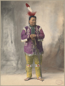 Colorized photograph of a Native American man, standing, propping his hands on a rifle that is pointed towards the floor.  He wears a large red and white feather in his hair, a purple shirt with white fringe, yellow pants with a beaded design on the knees, and beaded moccasins.