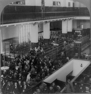 Black and white vintage photo of a view of the Ellis Island immigrant processing center, showing a room full of people being herded through a maze of waiting lines and gates