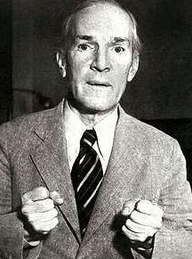 Black and white photo of Upton Sinclair, in a suit, looking straight into the camera.  Both his hands are formed as fists, as if he's sincerely trying to explain something