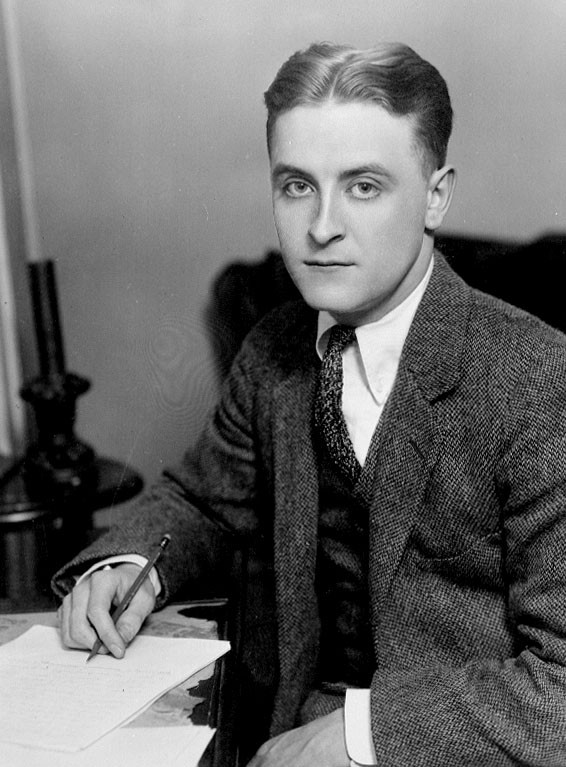 Black and white photograph of Fitzgerald as a young man, seated at a desk with pen in hand, looking at the camera