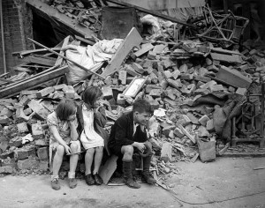 Black and white photo of three children sitting at the edge of a pile of rubble.  They all have their heads propped on their hands.  Furniture and other household goods are evident in the rubble.