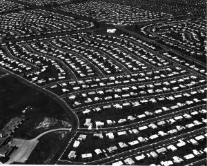 Black and white aerial photo showing hundreds of houses in a development, roughly centered around a larger white structure, possibly a school or church
