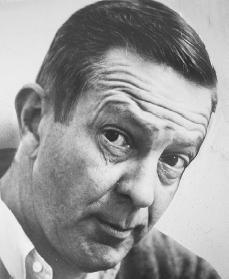 Black and white candid photo of John Cheever.  He is looking up at the camera with a raised eyebrow.