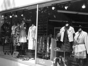 Black and white photo of a department store window display, showing several outfits on headless dressing dummies