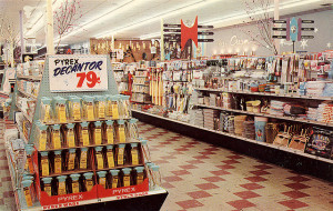 Photo of two aisles in a Piggly Wiggly supermarket in the 1950s.  Central in the frame is an end-cap display of Pyrex Decantors for 79 cents.