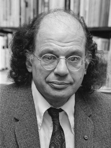 Black and white photo of Ginsberg, against a backdrop of books.  He is bald on top with shoulder-length hair on the sides, and wears wire-framed glasses and a suit.