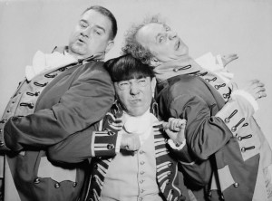 Black and white photo of The Three Stooges.  All are dressed in comedic military costumes with ruffles and buttons on their jackets.  Curle and Larry are squeezing against Moe, squished in the middle with a pained expression on his face.