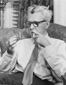 Black and white photo of Thurber, who is seated in a wing chair looking at a lit match he holds in one hand; his other hand holds a cigarette to his lips.  He has unkempt white hair with a dark streak in the center of his forehead.  He wears dark patterned glasses, a white button-up shirt and a tie.