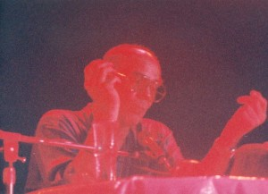 Low-quality photo showing Thompson seated at a table in front of a microphone.  His figure appears in red tones, and the background is purple.