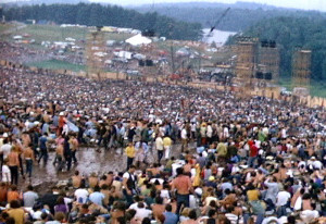 Photo of a crowd scene on a hillside.  A path through the middle of the crowd is very muddy.  A stage appears at the bottom of the hill, with a lake and woods behind it.