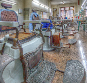 Photo of the interior of an antique barber shop, showing a line of antique barber chairs facing a mirrored wall
