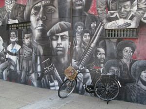 Photo of a wall mural depicting figures from the Black Panther movement, many African-American men with Afros or wearing berets.  The central figure looks into the street and holds a machine gun.  A bicycle is parked in front of the mural.