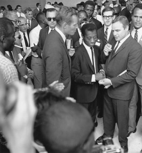 Black and white photo showing James Baldwin, a short man in a suit with a big smile, standing between Charlton Heston and Marlon Brando. A large crowd surrounds them.