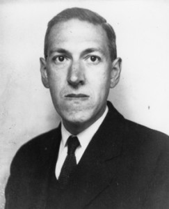 Black and white photo of Lovecraft.  He has a stern expression as he stares into the camera.  He wears a dark suit and is standing against a plain white background.