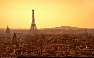 Photo of Paris skyline, looking down from a distant hill.  The Eiffel Tower stands dominant towards the left.  The sky is bright yellow, and the city is hazy amber.