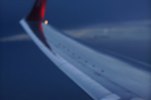 Photo of a wing of a plane, taken from inside the cabin.  The sky is dark and the focus is soft.