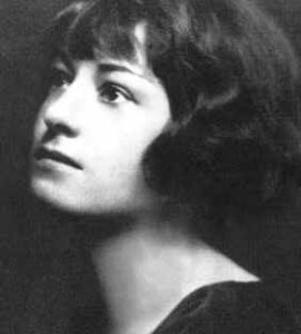 Black and white head shot of Dorothy Parker.  She has ear-length dark hair waved around her face, and short bangs.  She wears a dark top covering her shoulders, with an open neck.  She stares off to the left, looking up.