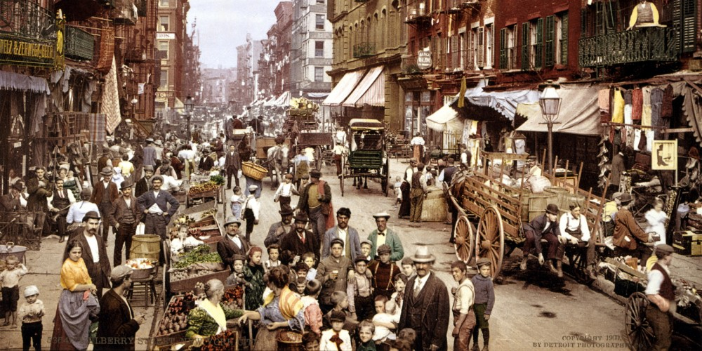 A crowded New York City street with many shops and crates of fruit.