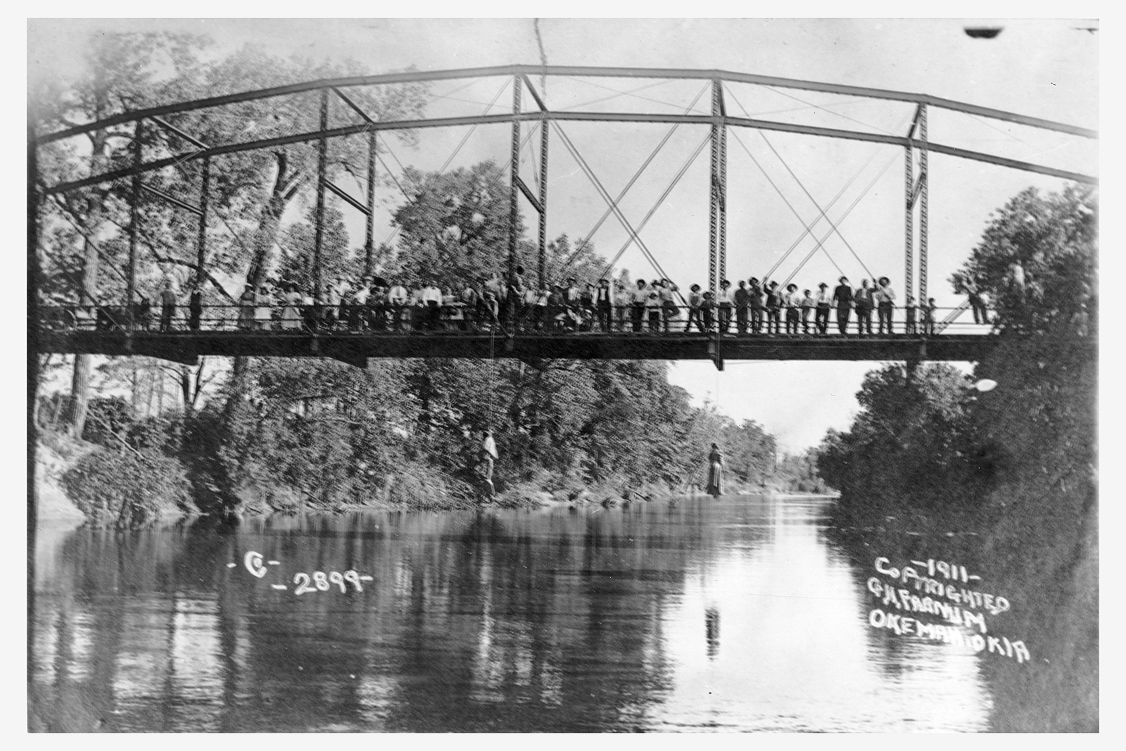 A photograph of a crowd of people standing on a bridge, from which two dead black people are dangling.