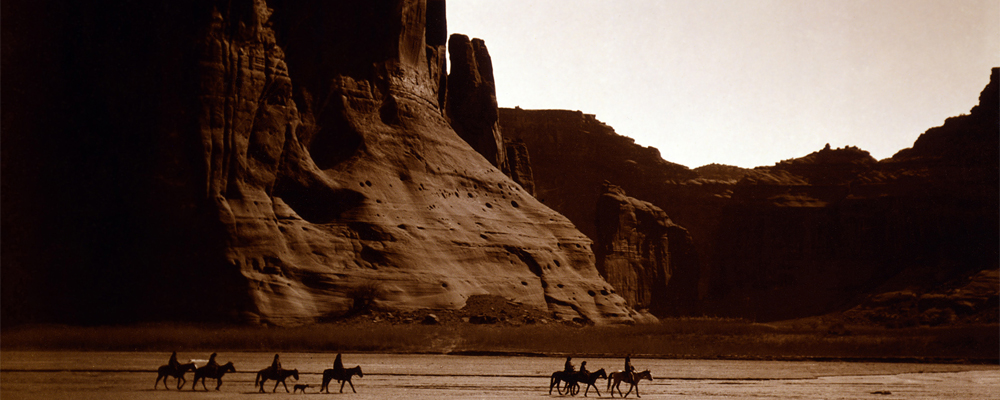 Silohouetted people on horses near the walls of an enormous canyon.