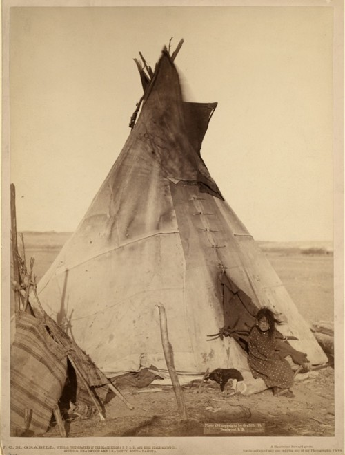 A young Oglala girl sitting in front of a tipi.