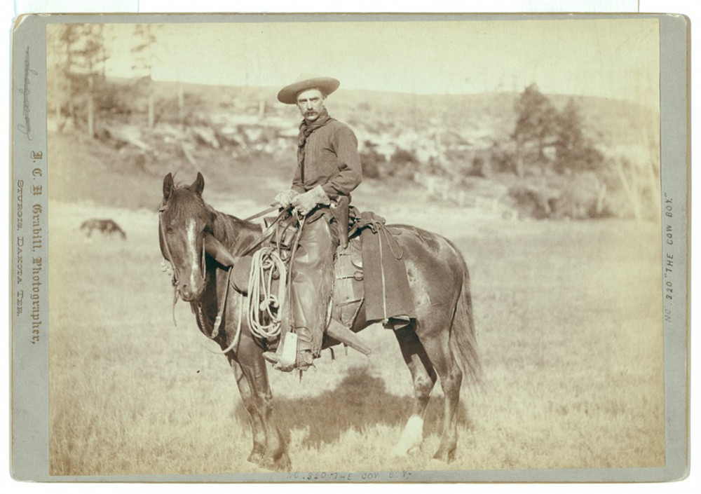 A photograph of cowboy on a horse.