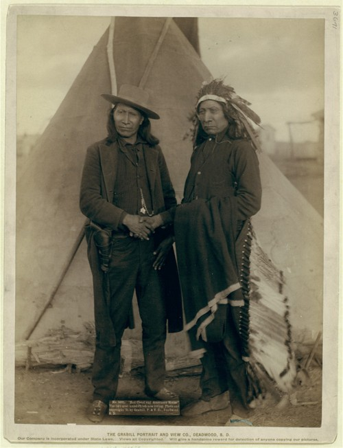 Red Cloud and American Horse, in Western-style clothing, shake hands.
