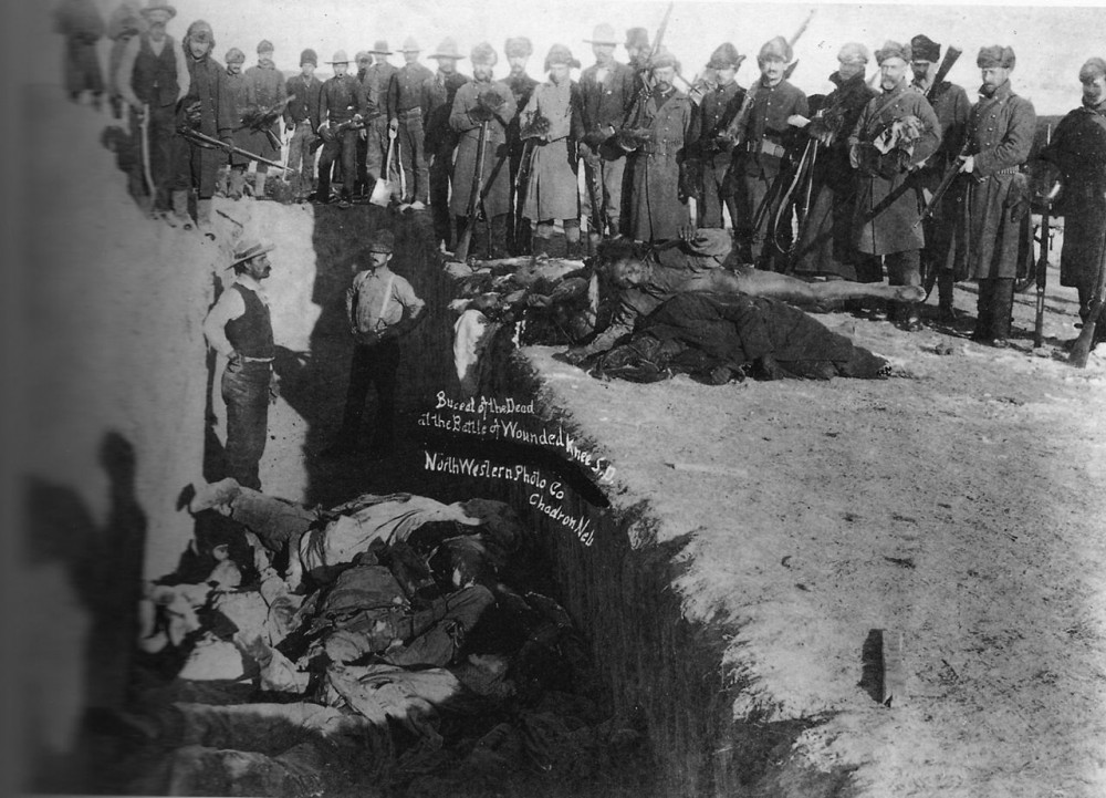 U.S. Soldiers putting Indians in common grave; some corpses are frozen in different positions.