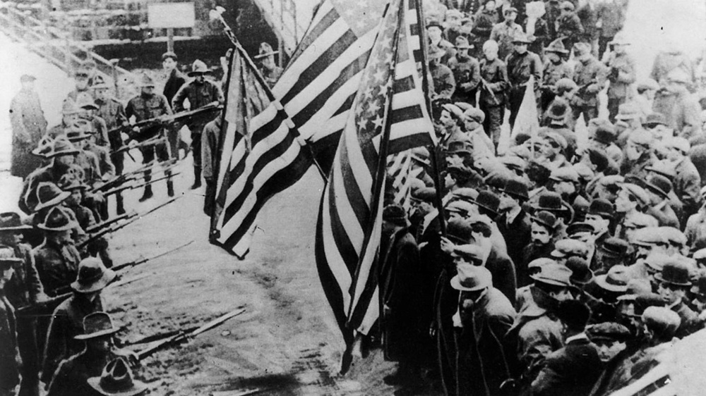 A group of people holding large American flags face off with a smaller group of people holding bayonets.