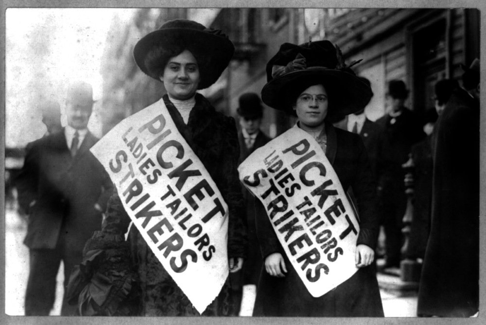 Two women wearing banners that say Picket Ladies Tailors Strikers.