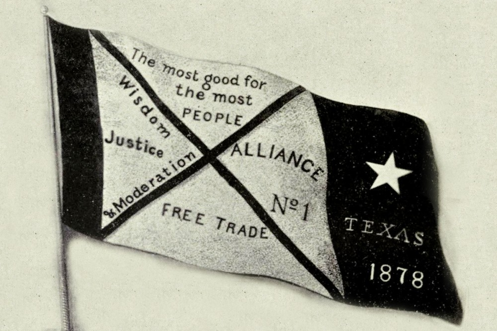 A flag with a dark thin stripe, a white square with an X, and a thick dark bar with a single star and the words Texas 1878. The light area with the X is divided into sections. One section says The most good for the most people. Another section says Alliance number one, and another section says Free Trade. The last section says wisdom, justice, and moderation.