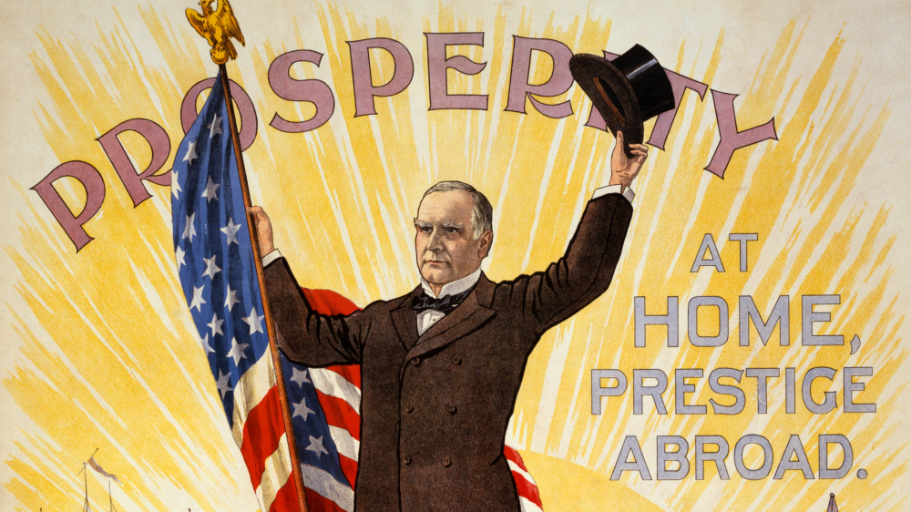 William McKinley holds an American flag in one hand and his hat in the other. The sun rises behind him. Around him are the words Prosperity at home, prestige abroad.