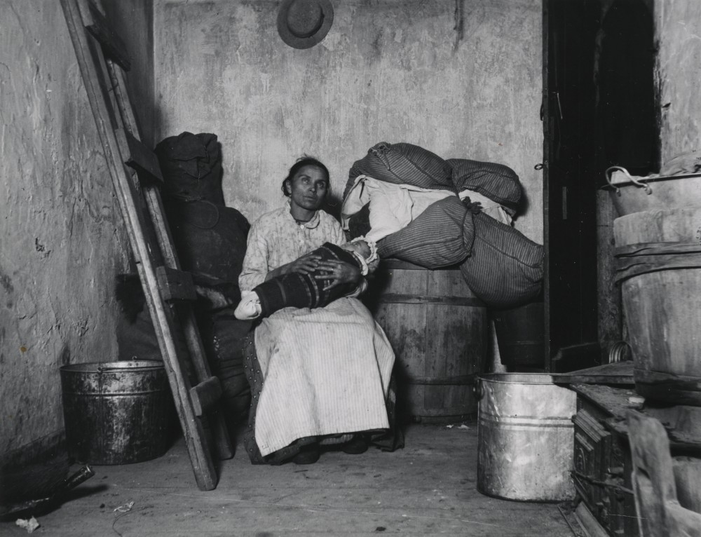 A woman holding a baby sits in a room full of sacks and barrels.