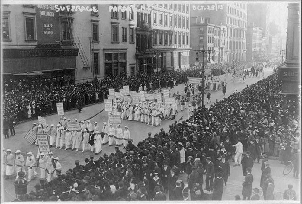 A group of women dressed alike and holding signs parade down a street filled with onlookers.