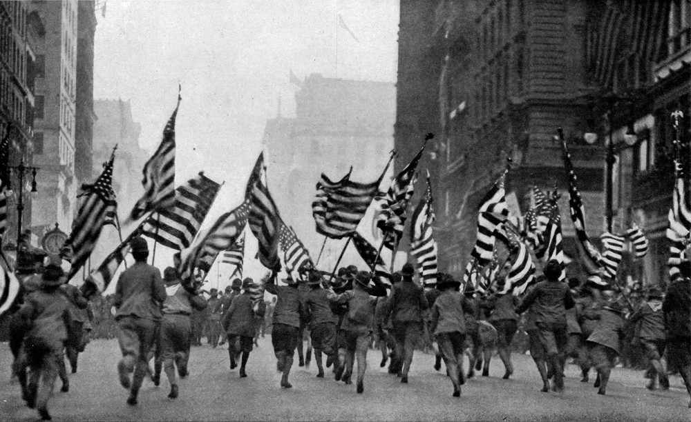 A crowd of people running down the street while holding America flags.