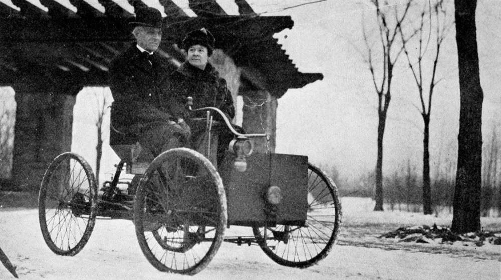 A couple on an early automobile. It has a seat on top of four bicycle wheels. There are no walls, doors,  or roof.
