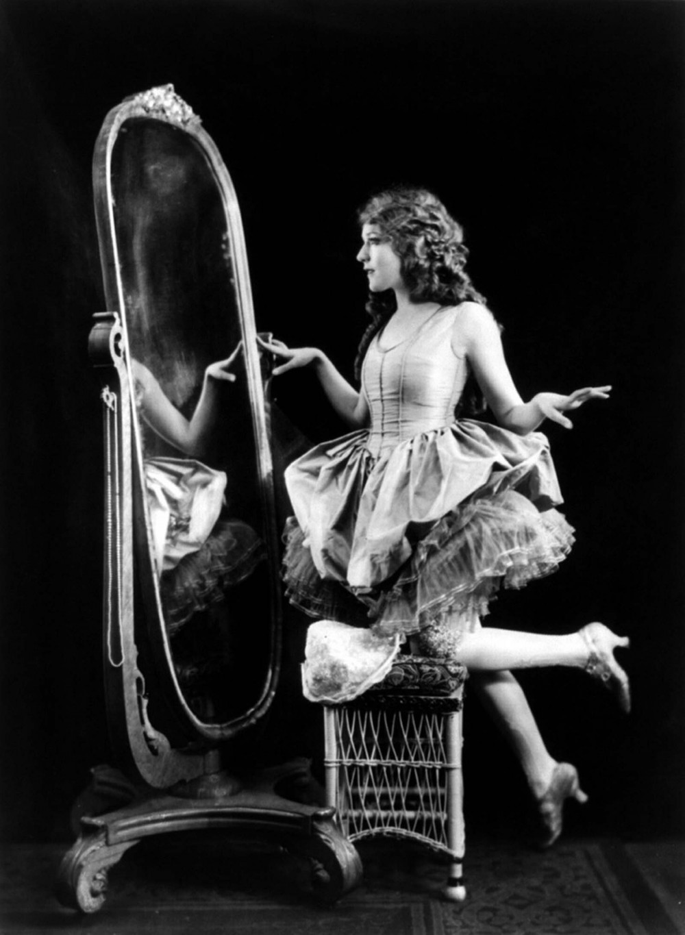 Mary Pickford posing by a full-length mirror and wearing a knee-length dress.