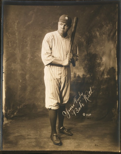 Signed photograph of Babe Ruth in his baseball uniform and holding a baseball bat.