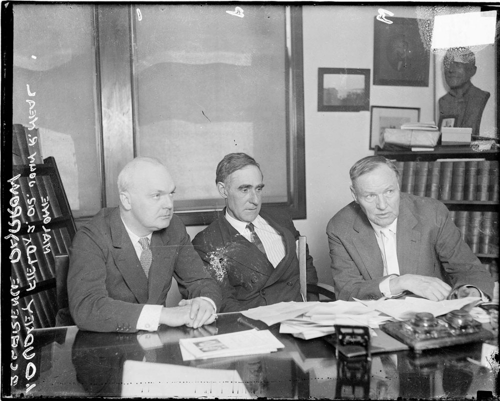 Three men in suits at a table filled with papers.