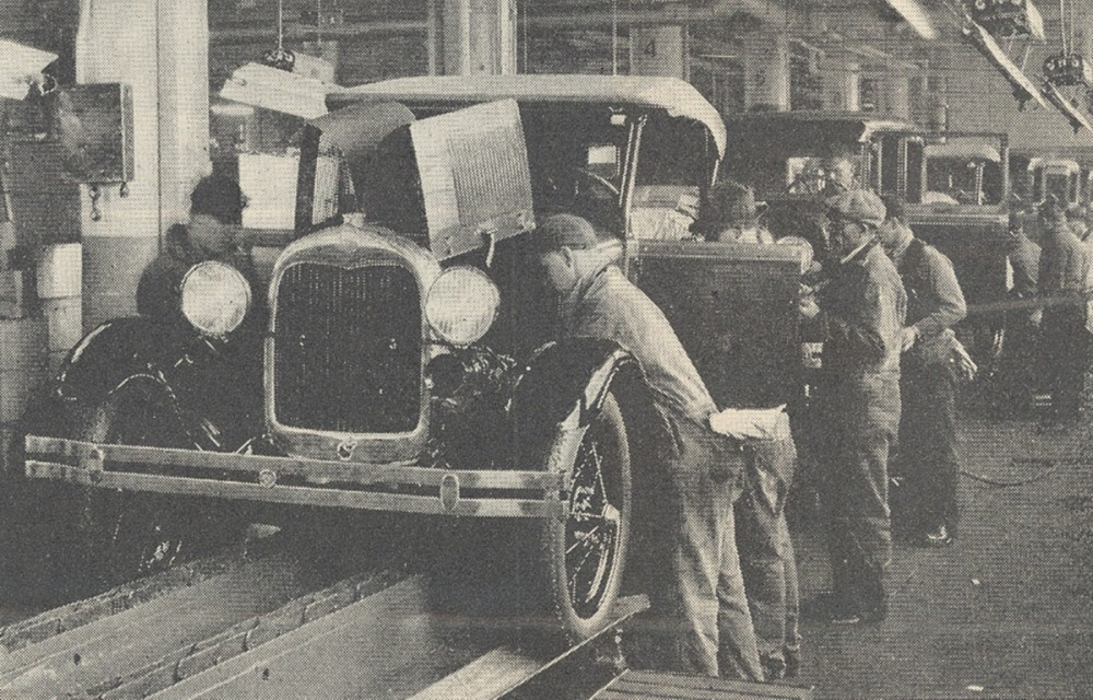 Men positioned along an assembly line for Ford automobiles.